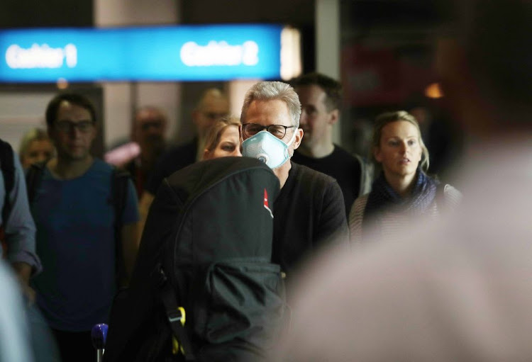 Passengers arrive from Hong Kong at Cape Town International Airport, on January 29 2019, after being screened by health officials following the outbreak of the coronavirus in China.