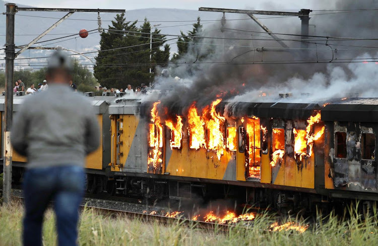 A crowd gathered to watch flames consuming a train between Kentemade and Century City stations, in Cape Town, on January 25 2020.